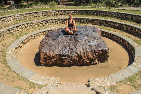 El meteorito más grande del mundo en Grootfontein, Namibia. Una enorme pieza de hierro procedente del espacio. Turista chica blanca sentada en un meteorito