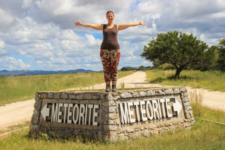 The largest meteorite in the world at Grootfontein, Namibia. White girl tourist stands on the sign
