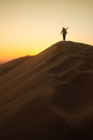 The highest sand dunes in the world at sunset in Namib Desert, in the Namib-Nacluft National Park in Namibia. Sossusvlei. Young woman tourist with backpack stands on top Banque d'images