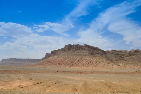 Desert landscape with rocks and geological formations on a hot summer day on the road from Kerman to Mashhad. Desert of Iran.