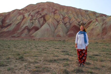 Stunning unusual colored mountains in Iran near Tabriz. Turis man on a background of mountains. Natural attractions of Iran. Hiking in Iran. Young girl tourist on a background of colored mountains.
