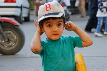 Shiraz, Iran - May 10, 2017: a cute Iranian baby boy in a cap and a bright T-shirt with huge brown eyes smiles shyly and poses for the camera in the city. Editöryel