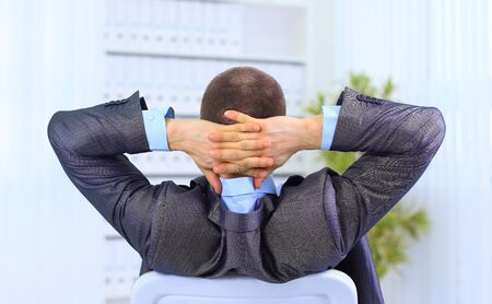Rear view of businessman with hands behind head