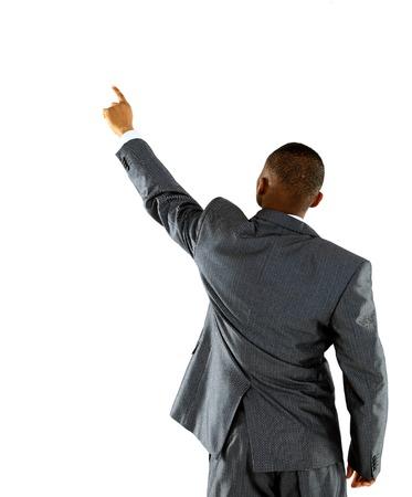 アフリカの実業家が壁を指します。リアビュー。白で隔離されました。