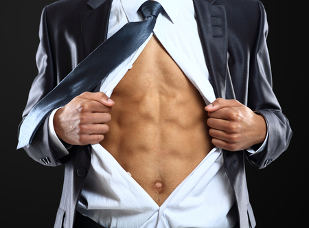 Business man tears open his shirt in a super hero fashion getting ready to save the day isolated over white background  Stock Photo