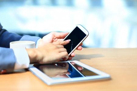 現代の携帯電話でデジタル タブレット コンピューターを使用しての実業家。成功のワークフローの概念のための新しい技術。