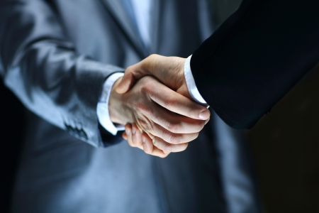 black handshake: Handshake - Hand holding on black background Stock Photo