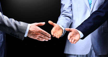shaking: Two business men shaking hands to their leader, close up
