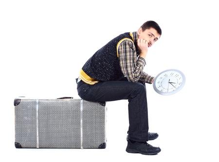 大時計は、白で分離を保持している、空港で待っている若い男