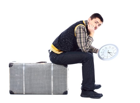 Young man waiting at airport, holding big clock, isolated over white