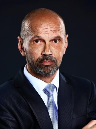 Portrait of senior confident businessman on dark background photo