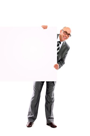 Portrait of happy smiling young business man showing blank signboard, isolated over white  photo