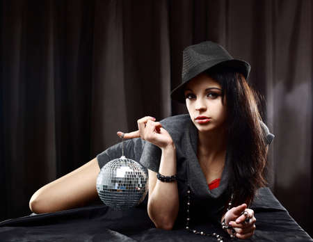 Sexy lady with shiny disco ball, lying on the table, against dark background  photo
