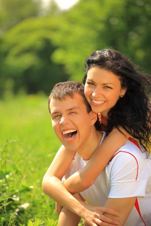 Portrait of happy young couple enjoying backriding outdoors photo