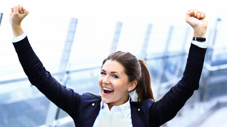Successful business woman with arms up celebrating outdoor