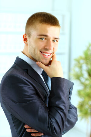 Closeup of a young smiling business man standing in a light and mordern business hall.  photo