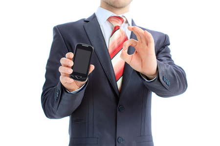 closed fist sign: Business man showing ok sign with his mobile phone