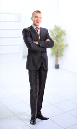 Young smiling business man standing in a light and mordern business hall   photo