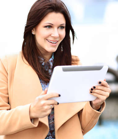 world at your fingertips: Businesswoman in coat working on digital tablet out of office overlooking cityscape