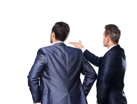Two business mans from the back - looking at something over a white background photo