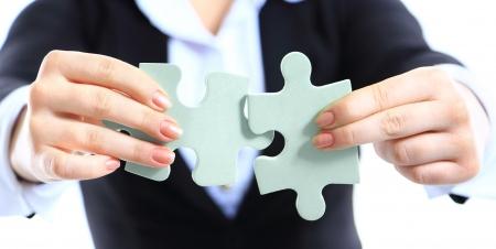 ビジネスの女性は、2 つのジグソー パズルのピースを示します。ビジネスの強みと成功のコンセプトです。