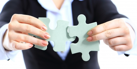 Business woman showing two jigsaw puzzle pieces . Concept for business strength and success.