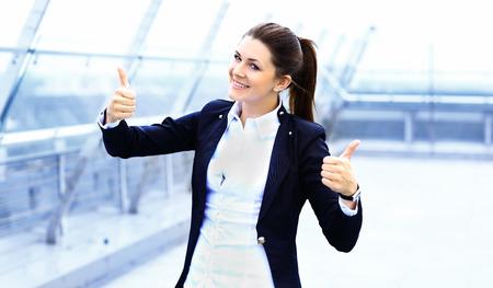 カジュアルなビジネスの女性の親指は幸せそうに見えて上げますと