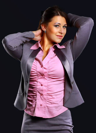 Studio portrait of a businesswoman in suit, against dark background photo