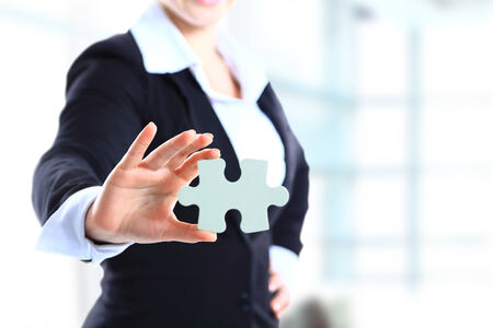 Business woman holding a piece of puzzle Stock fotó