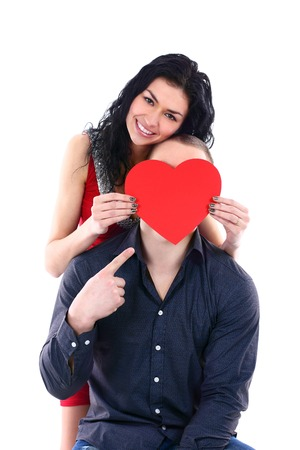 hides: A beautiful young woman hides her face behind a guy with a big red heart