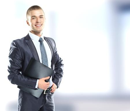 幸せな実業家で、事務所でポーズをとって青フォルダー