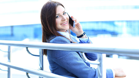Pretty young business woman using mobile phone outdoor photo