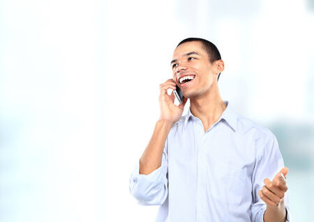 Successful African American businessman or man talking on his cell phone in a modern office photo