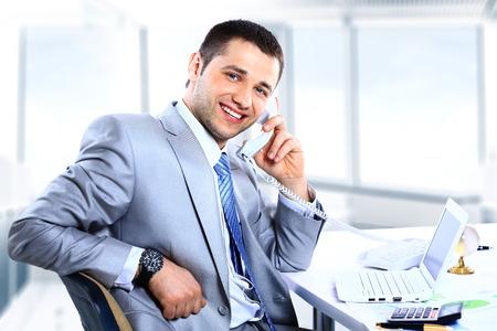 事務所の電話に答えることで陽気な男 写真素材