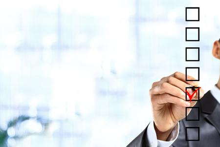 Jonge zakenman controle stempel op checklist met marker.