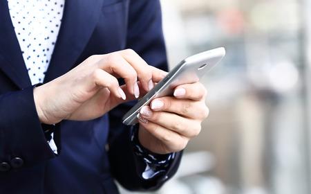 モバイルのスマート フォンを使用してビジネスの女性のクローズ アップ
