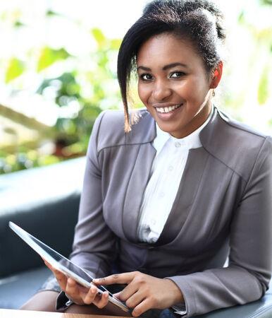 デジタル タブレットを使用して近代的なオフィスに座っている実業家