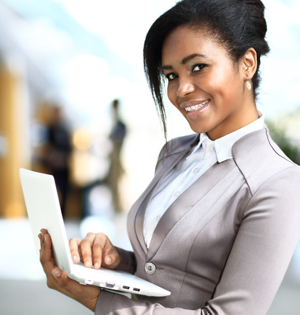 Business woman standing in foreground with laptop in her hands, her co-workers discussing business matters in the background, tilt up photo