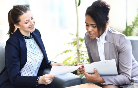 matters: Businesswomen With documents and folder Sitting In Modern Office and discuss business matters Stock Photo