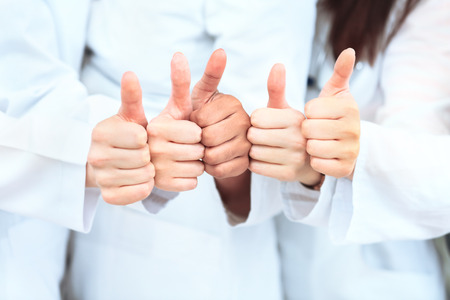 Portrait of confident doctors team showing thumbs up while standing in a row at clinic photo