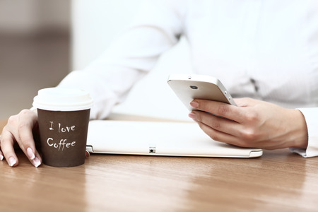 Close-up Of Woman Holding Mobile Phone In Front Of Coffee Cup photo
