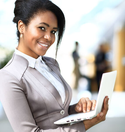 Smiling african businesswoman with laptop computer photo