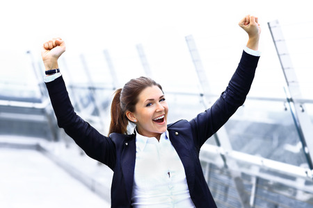 accomplishment: Successful business woman with arms up celebrating