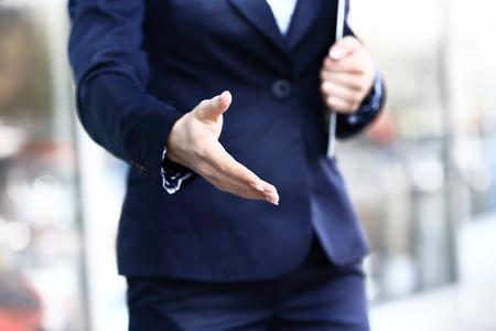 握手のために伸ばした腕を持つ女性実業家 写真素材