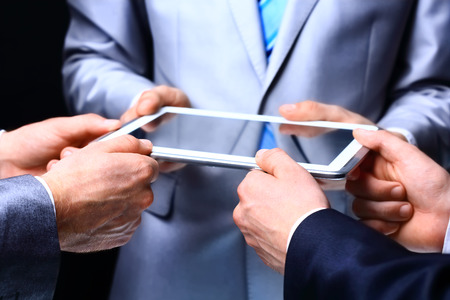 demonstrated: Modern people doing business being demonstrated on the screen of a touch-pad