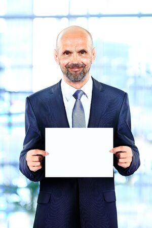 Happy senior businessman holding Blank business card in the office photo