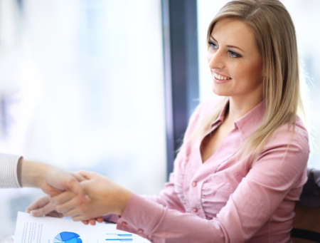 trust people: Business woman smiling and doing a handshake in the office
