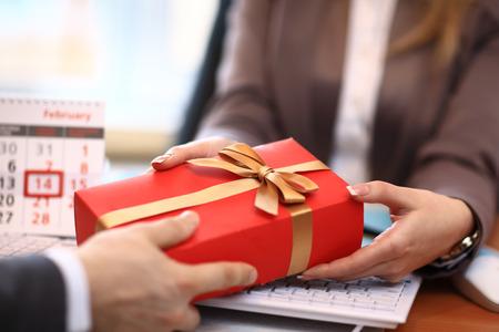 ビジネスの男性が女性に贈り物を提供して 写真素材