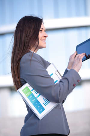 Businesswoman working on digital tablet outdoor over modern building background Stock Photo