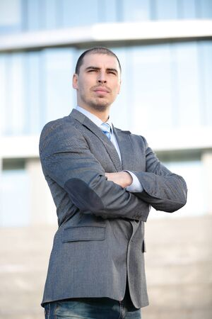 Caucasian young businessman at oudoor over modern building background